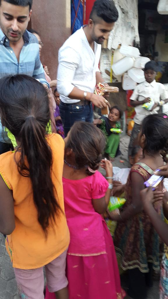 Gautam and Ravi handing out chips, biscuits and water to children
