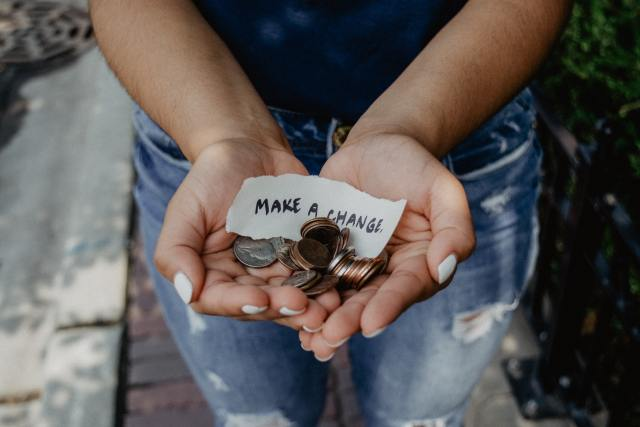 Person holding slip of paper saying Make a Change Photo by Kat Yukawa on Unsplash
