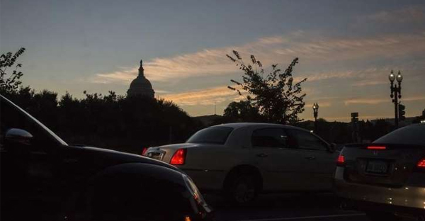 Cars wait at a traffic light as the sun rises over the U.S. Capitol dome in Washington, October 18, 2013. (REUTERS/Jonathan Ernst)