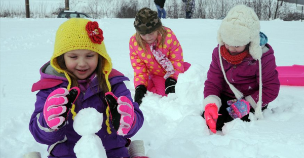 Onaleigh Barnes, Ava Hughes and Cadence Barnes, from left, build small snow men. (AP)