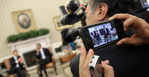 A journalist uses his phone to photograph U.S. President Barack Obama (R) meeting with Mexican President Enrique Pena Nieto (L) in the Oval Office of the White House January 6, 2015 in Washington, DC. (Win McNamee/Getty Images North America)