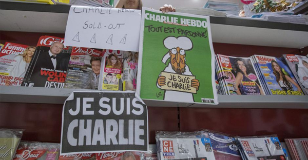 "An employee at a bookstore shows her last copy of the latest issue of satirical French weekly Charlie Hebdo, headlined ""Tout est pardonne"" (""All is forgiven""), along with a caricature of the Prophet Muhammad, at a kiosk on January 15, 2015. (YVES HERMAN/REUTERS)"