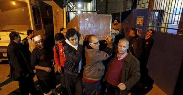 The coffin of Shaimaa el-Sabagh is carried out of the Zenhom morgue in Cairo, Egypt early Sunday, Jan. 25, 2015. (AP Photo/Ahmed Abd El-Gwad, El Shorouk Newspaper)