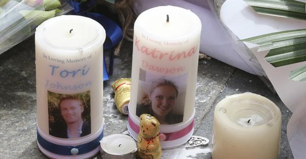Two candle tributes with photos of siege victims Tori Johnson left, and Katrina Dawson near the Lindt cafe in Sydney. (ASSOCIATED PRESS)