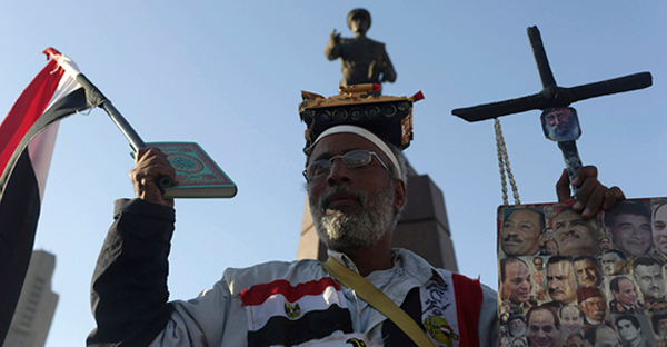 A supporter of Egypt's former army chief Field Marshal Abdel Fattah al-Sisi holds a Koran, a cross and flags as he celebrates the announcement of his candidacy for presidential election in Tahrir square in Cairo on March 28, 2014. (REUTERS/Asmaa Waguih)