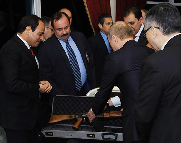 Egyptian President Abdel-Fattah el-Sissi (left) gives an assault rifle to Russian President Vladimir Putin upon his arrival at the Cairo International Airport in Egypt on Monday.