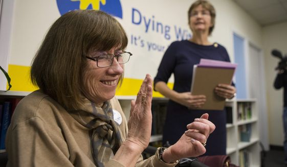 Linda Jarrett, left, applauds Wanda Morris, right, CEO of Dying with Dignity, as she speaks to the media group's offices in Toronto.