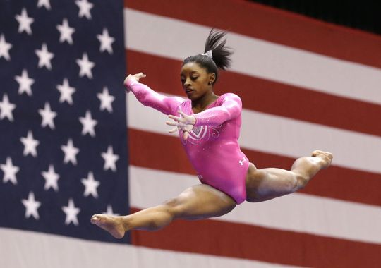 Simone Biles jumps off the balance beam during the American Cup. Biles led from the start in a record-setting win at the American Cup in her first competition since winning two consecutive world all-around title last year. (Photo: LM Otero, AP)