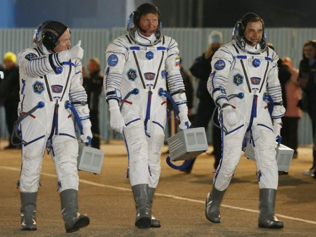 Scott Kelly, left, and Russian cosmonauts Gennady Padalka and Mikhail Kornienko walk at the sending-off ceremony before boarding their Soyuz TMA-16M rocket. (Photo: Sergei Ilnitsky, European Pressphoto Agency)