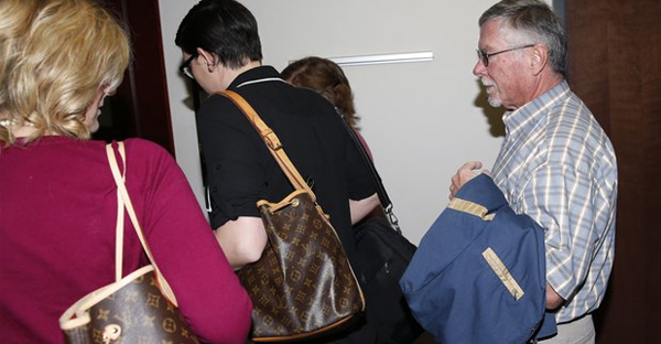 """In this file photograph taken on Monday, Dec. 8, 2014, Robert Holmes, far right, father of theatre shooting suspect James Holmes, heads into a pre-trial readiness hearing in Centennial, Colo., in the murder trial of his son, who is charged with killing 12 moviegoers and wounding 70 more in a shooting spree in a crowded theatre in Aurora, Colo., in July 2012. Bob Holmes and his wife Arlene, told the Del Mar Times in the couple's first interview since the theatre massacre that Arlene Holmes has written a book and says that she prays for the victims daily """"by name and by wound."""" (PHOTO CREDIT: AP Photo/David Zalubowski, File)"""
