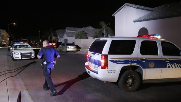 A Phoenix Police officer walks in front of the blocked off street near a home where authorities say five people were killed inside after a shooting. (AP)