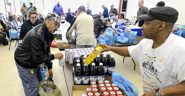 Volunteer David Randolph distributes food to clients Thursday at the monthly food pantry sponsored by Pastor Dai Morgan's Living Spirit Ministry, formerly the Swissvale United Methodist Church. The church operates from empty store fronts in Swissvale after selling its dedicated church building. (Bob Donaldson/Post-Gazette)