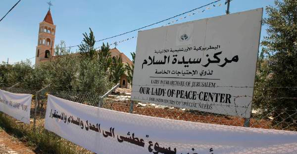 """A sign with Arabic writing """"Palestine the land of Jesus is eager for justice, peace and stability"""" is seen at the Lady of Peace church, background, in Amman, Jordan. (AP Photo)"""