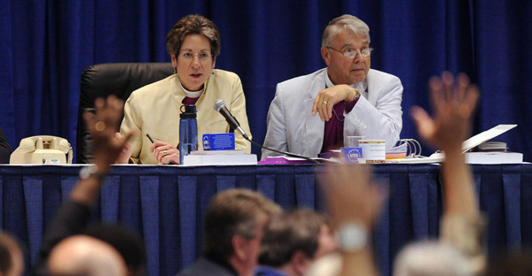 Presiding Bishop Katharine Jefferts Schori, top left, and John C. Buchanan, interim bishop of Quincy, Ill., watch over a show of hands in the House of Bishops at the 76th General Convention of the Episcopal Church in Anaheim, California, Monday, July 13, 2009. Church leaders will convene again on Monday in Salt Lake City. (Chris Pizzello, AP)