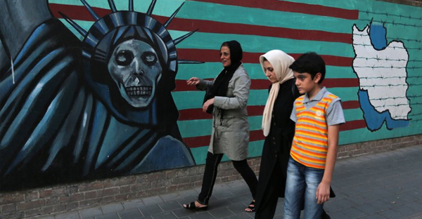"An Iranian family walks past anti-U.S. graffiti on the wall of the former U.S. embassy in Tehran on Tuesday. President Hassan Rouhani told Iranians that ""all our objectives"" have been met by a nuclear deal agreed upon Tuesday after talks with six world powers, including the U.S. (Atta Kenare/AFP/Getty Images)"