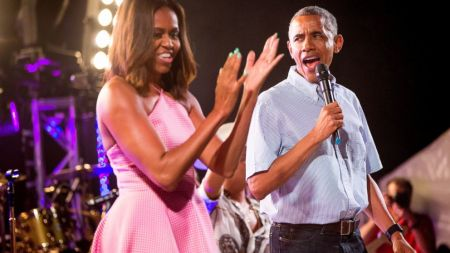 President Barack Obama, accompanied by first lady Michelle Obama, left, speaks during an Independence Day celebration on the South Lawn at the White House in Washington, Saturday, July 4, 2015. (PHOTO CREDIT: AP Photo/Andrew Harnik)