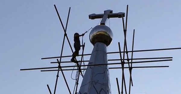 A cross atop the Lower Dafei Catholic church topples after being cut down by a Chinese government worker in eastern China's Zhejiang Province in July. (Didi Tang/AP)