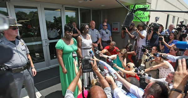 Nadine Collier, (in the green dress) youngest daughter of shooting victim Ethel Lance, addressed the media after speaking about forgiveness at a bond hearing for accused killer Dylann Roof. (Leroy Burnell/Staff)