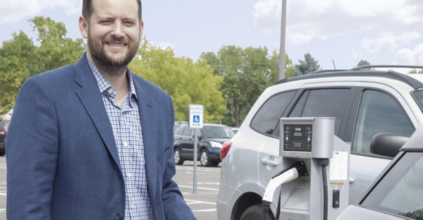 Pastor Jonathan Wiggins recharges his BMW i3 electric car in Resurrection Fellowship Church parking lot.