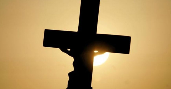 A cross is silhouetted against the sun in Pinellas Park, Fla. (AP Photo/Evan Vucci)