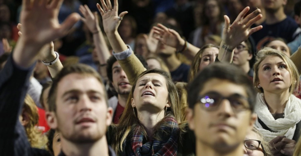 Students sing and pray prior to a speech by Republican presidential candidate Ben Carson at Liberty University in Lynchburg, Va., on Wednesday, Nov. 11, 2015. (AP Photo/Steve Helber)