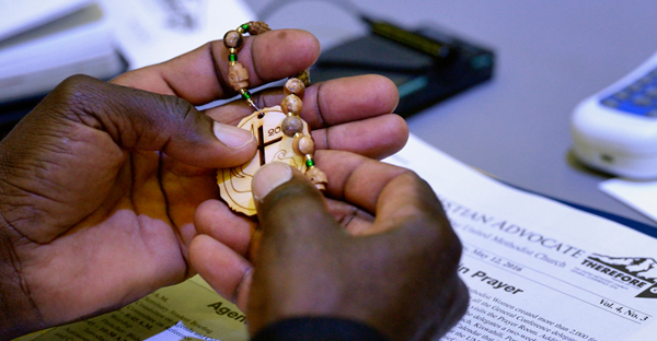 A delegate handles prayer beads during prayer on May 12, 2016 during the United Methodist General Conference in Portland, Ore. (Photo by Paul Jeffrey, courtesy of United Methodist News Service)