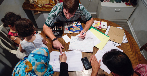"""A family of refugees receiving an English lesson from William Stocks, 23, in Marietta, Ga. """"My job is to serve these people,"""" Mr. Stocks said, """"because they need to be served."""" (Credit: Dustin Chambers for The New York Times)"""