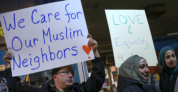 Demonstrators hold signs during a protest against President-elect Donald Trump and in support of Muslim residents in downtown Hamtramck, Mich., on Nov. 14, 2016. (Photo courtesy of Reuters/Brittany Greeson)