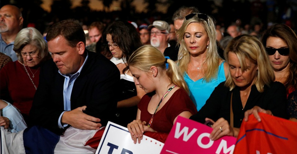 Trump supporters pray before a rally in Florida. (Carlo Allegri / Reuters)