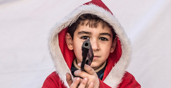 Kayaks, 7, poses for a picture holding tiny gun in a camp where Christians displaced by Islamic State militants are living, in Irbil, Iraq, Friday, Dec. 23, 2016. Iraq's Christians are marking the holiday in his camp for displaced people with a sense of worry and despair, unable to return to their towns they were forced to flee two years ago by the Islamic State group's onslaught. (AP Photo/Manu Brabo)