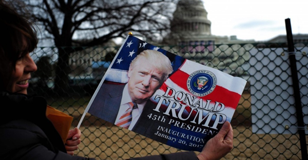 Third-grade teacher Kimi Moro of California poses with a flag bearing the image of President Trump near the Capitol. (Jewel Samad/Agence France-Presse via Getty Images)