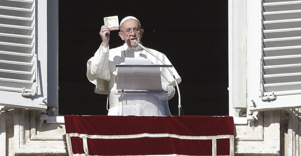 Pope Francis shows a booklet on Jesus Christ that will be distributed to faithful during the angelus prayer from his studio's window overlooking St. Peter's square, at the Vatican, Friday, Jan. 6, 2017. (AP Photo/Andrew Medichini)