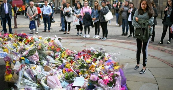 Members of the public pause to look at floral tributes and messages in St Anns Square on May 24, 2017 in Manchester, England. An explosion occurred at Manchester Arena on the evening of May 22 as concert goers were leaving the venue after Ariana Grande had performed. Greater Manchester Police are treating the explosion as a terrorist attack and have confirmed 22 fatalities and 59 injured. (Jeff J. Mitchell/Getty Images)