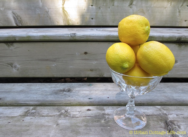A small crystal dish piled high with lemons sits on wooden steps.