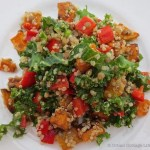 Overhead view of kale, quinoa and roasted sweet potato salad with bright pops of red pepper on a white plate.