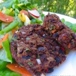 Black bean sweet potato cakes on a a bed of salad on a white plate