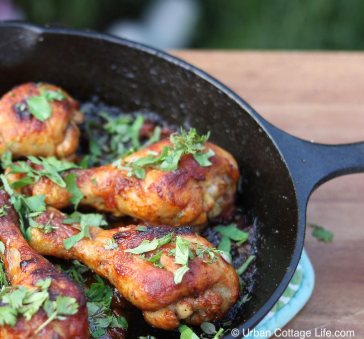Glazed chicken drumsticks garnished with chopped herbs in a cast iron skillet.