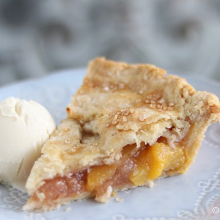 A slice of peach pie with a flaky pastry and a scoop of vanilla ice cream sits on a pale blue plate embossed with a decorative pattern