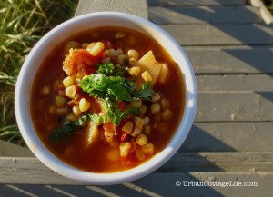A bowl of colourful grilled corn soup topped with a sprig of basil balances on a railing besides the weathered steps leading down to the beach.