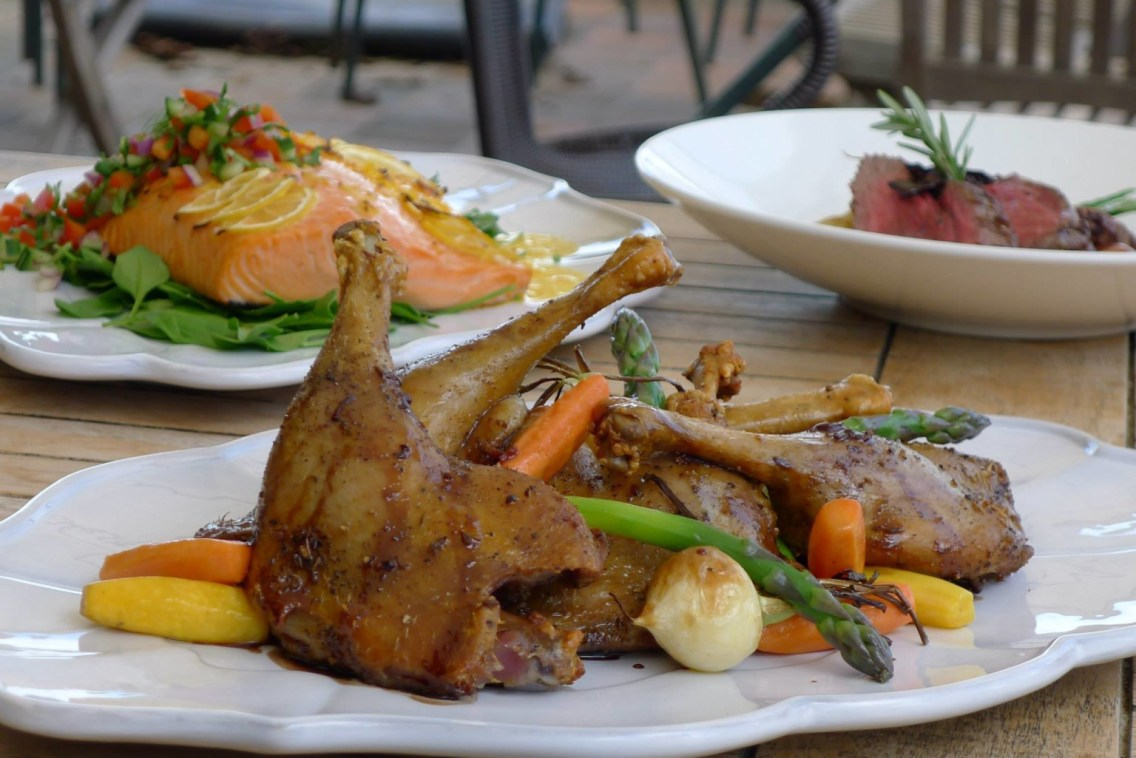 Roast Chicken on a white serving plate with asparagus, carrots, yellow courgettes and onions
