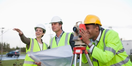 Architect and engineers with blueprint and theodolite in field