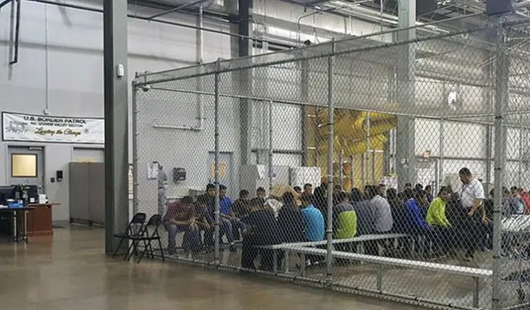 Detained immigrants pass their time behind metal fencing similar to a cage. (Credit: US Customs and Border Protection)
