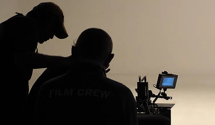 Silhouette of working people or production film crew are making (Credit: Deposit Photos)