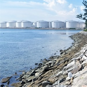 View from shore of a seawall and oil storage containers in the background