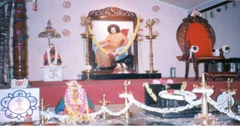 """Inside the Sai center in Indiranagar. The altar area contains a photograph of Sathya Sai Baba placed for worship, a chair signifying his """"presence,"""" and a small image of Shirdi Sai Baba (Sathya Sai Baba is believed by his devotees to be a reincarnation of this Maharashtrian holyman)."""