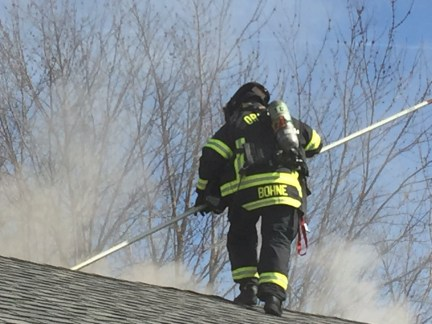 Fireman fighting a fire on the roof of a house
