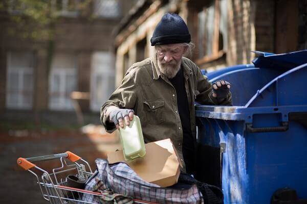 Homeless Man Digging Through The Trash
