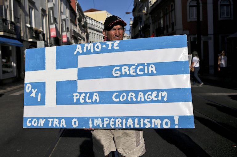 """Португалец носи транспарант на гръцкото знаме с надпис: """"Обичам те Гърция, за куража срещу империализма""""  ©EPA/БГНЕС"""