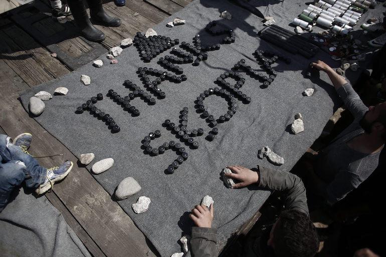 Деца бежанци са използвали гилзи от сълзотворен газ и гумени патрони за този надпис. ©EPA/БГНЕС