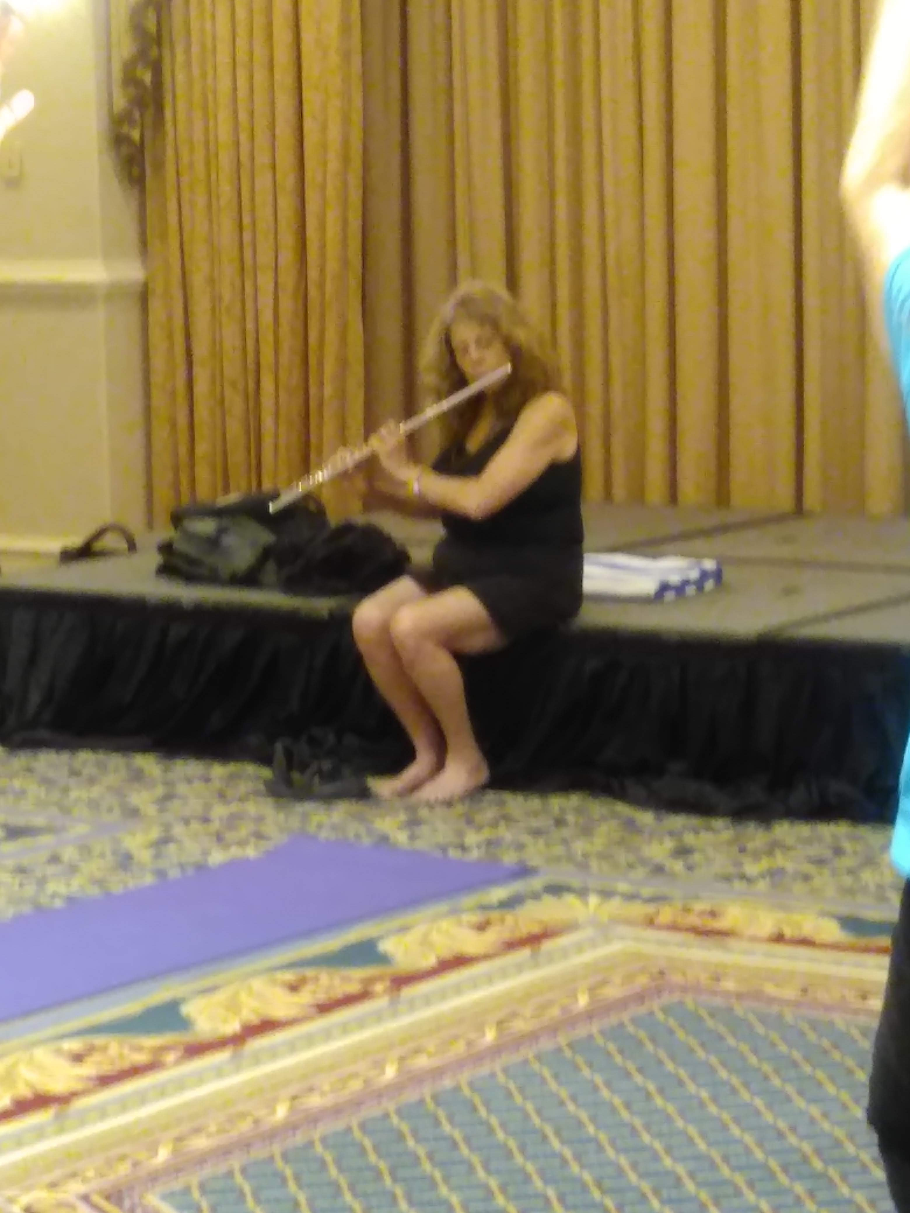 Marla is playing the flute at the Rise And  Shine Yoga with Tinoca at IAFC2019